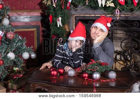 Family father and son sad on Christmas eve on the Christmas tree and the fireplace. The concept of an unhappy Christmas and New year.