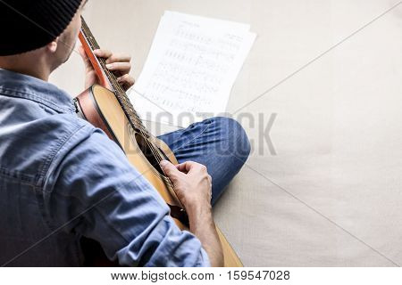 Singer songwriter plays song from sheet music tabs. Male guitar player in jeans  composing a song on acoustic guitar