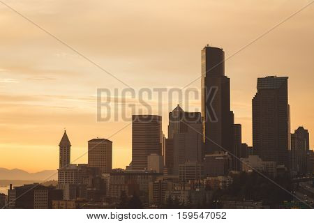 Seattle skyline with silhouettes of skyscrapers against cloudy evening sunset.