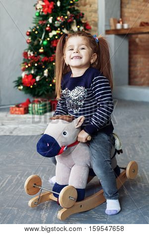 Happy little girl swinging on a horse. The concept of Christmas and New Year.