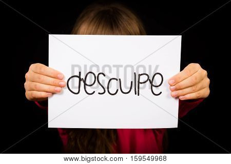Studio shot of child holding a sign with Portuguese word Desculpe - Sorry