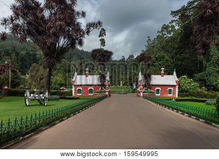 Nilgiri Hills India - October 25 2013: Wide gray walkway leads up to Heritage Gate at Ooty Botanical Garden. Small red houses against green background. Manicured lawns and cannon in foreground.