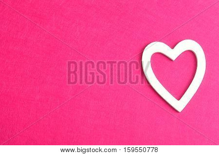 Valentine's Day. A white heart isolated against a pink background