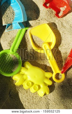 Colorful toys in children sandbox. Red, green, blue and yellow