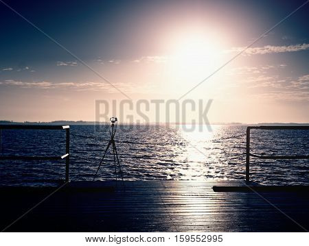 Tripod With Camera Ready On Pier, Sun Above Ocean. Empty Wooden Mole Board