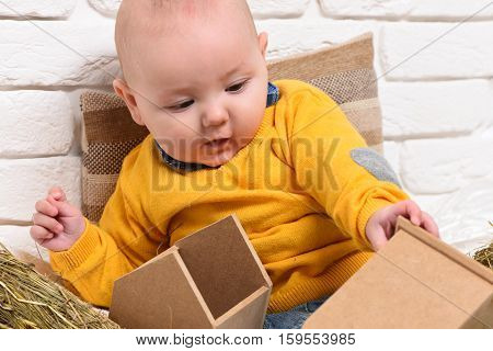 small baby boy with adorable curious face in yellow sweater leaned on pillow and playing with wooden box on white brick wall background