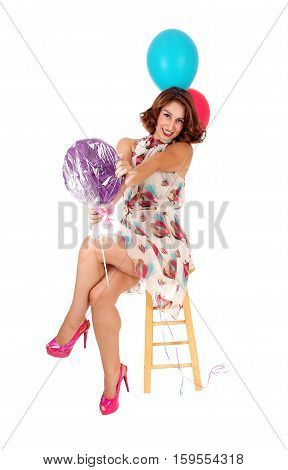 A beautiful young woman siting on a chair with legs crossed and holding a lollypop and two balloons isolated for white background.