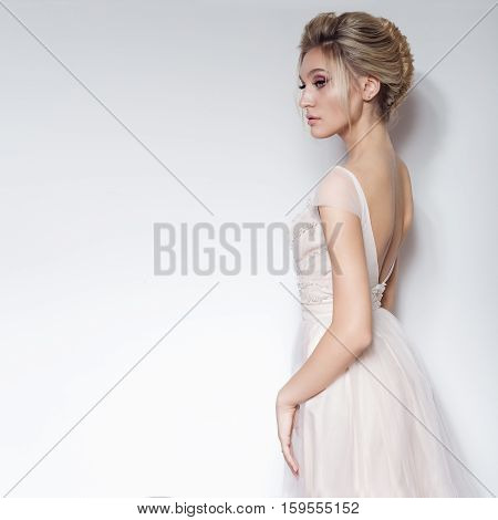 beautiful delicate bride sexy girl in soft pink skazachno wedding dress with a cut on the chest and back with makeup and evening hairstyle in the studio on a white background