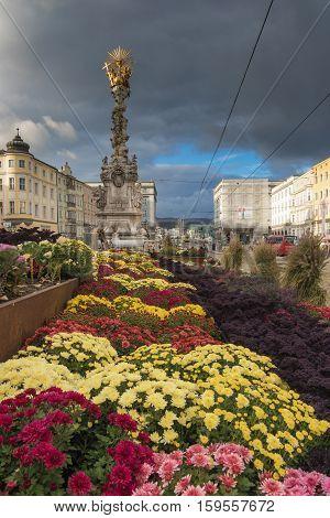 LINZ, AUSTRIA - October 30 2016: Baroque Trinity column and autumnal flower decoration on the main square (Hauptplatz) in Linz Austria
