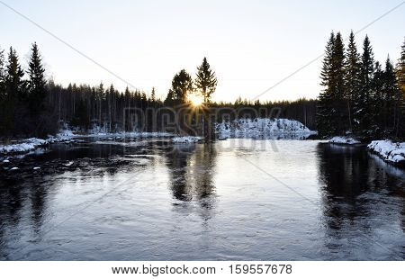 Little river with forest on both sides and the midwinter sun in the horizonpicture from the North of Sweden.