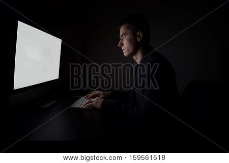 Man working lokking to the monitor screen and typing on computer keyboard during the night work in the office.