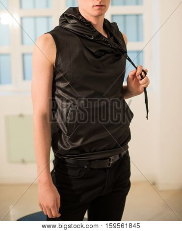 Men`s fashionable black leather sleeveless hoodie on the model