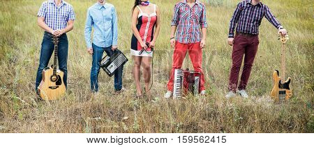 Concept photo of music band with guitars microphone and accordion standing outdoors