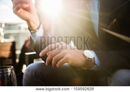 Lifestyle photo of elegant businessmen wearing luxury watch and having dinner in restaurant after succesful working day.