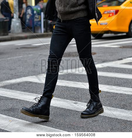 Men fashion concept. Man wear black stylish leather boots and walk outdoors.