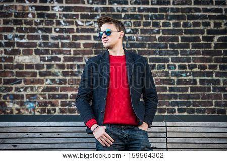 Fashionable young adult stylish man posing outdoors wearing red pulower jeans cotton jacket and sunglasses. Stylish handsome caucasian man with messy hairstyle.