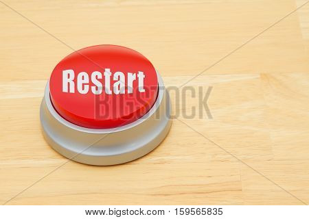 A Restart red push button A red and silver push button on a wooden desk with text Restart
