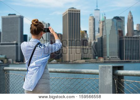 Tourist woman taking travel picture with camera of Manhattan Skyline and New York City skyline during autumn holidays. View from the back.