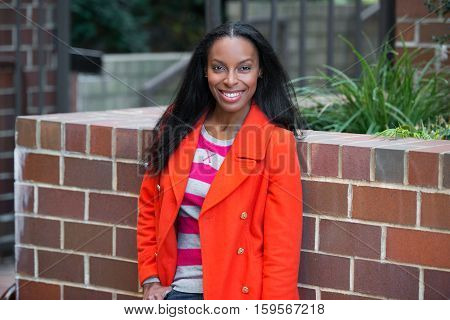 Happy beautiful african america woman wearing red jacket standing and smiling at student college campus.