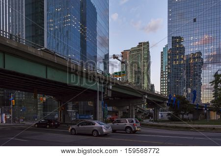 TORONTO,CANADA-AUGUST 1,2015:view of the traffic and urban life between skyscrapers in Toronto during a sunset from one of the central street of the city.