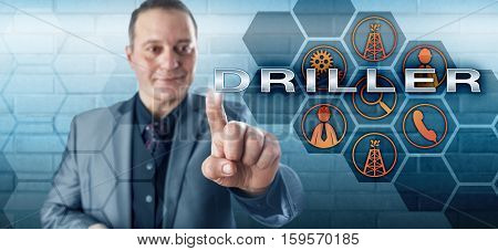 Smiling male oil well team leader with happy facial expression touching DRILLER on a virtual control screen. Oilfield terminology and petroleum industry concept for the drilling supervisor in charge.