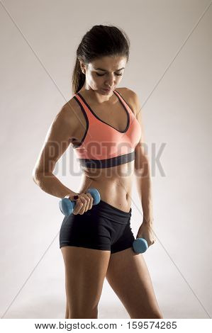 young attractive sport woman in fitness clothes smiling happy in aerobics training workout posing sexy holding weight isolated on grey background in sport healthy lifestyle concept