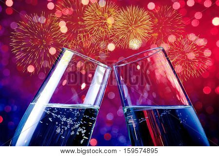 Champagne Flutes With Golden Bubbles On Red And Purple Light Bokeh And Fireworks Sparkle Background