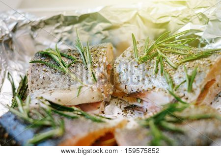 Raw fresh salmon steak pieces with rosemary ready for oven with sun flare