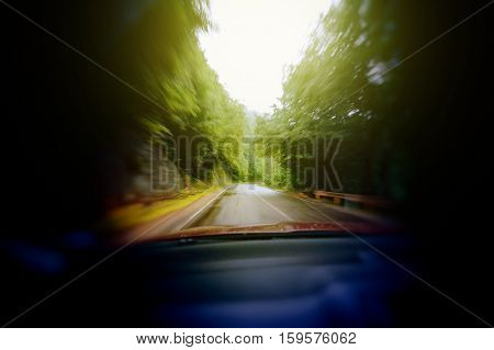 Blurred image of car headlights driving through forest - drunk scarry vision