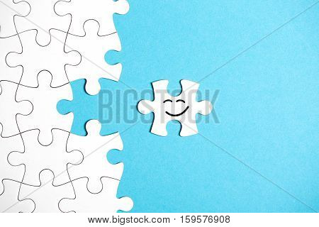 White puzzle with missing part on blue background. Missing part is happy to get back on her own place. Business concept