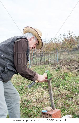 Elderly man cutting planks with axe on the field