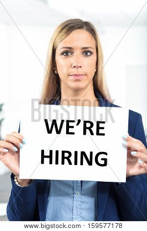 Woman Holding Hiring Sign In A Worklace Bacground