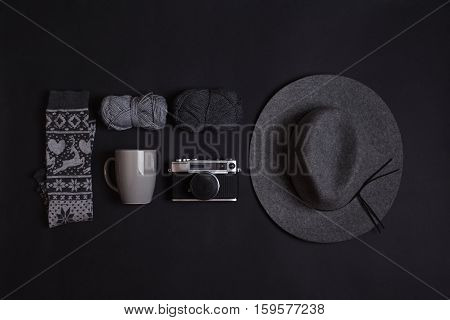 Minimalist setup of winter objects in gray. Vintage analogue camera, floppy hat, two wool yarns, winter print socks and coffee mug on black background. High angle view.