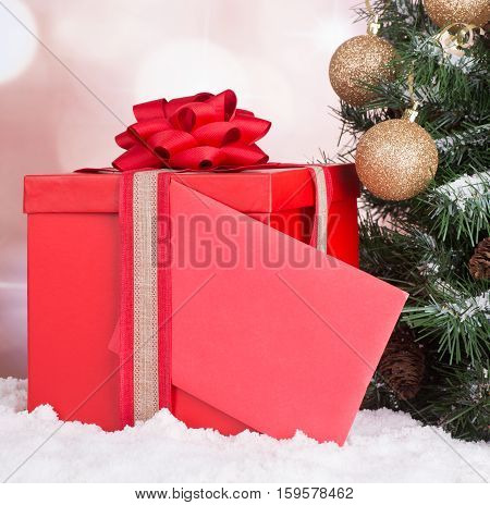 Red gift box with a blank envelope next to a Christmas tree