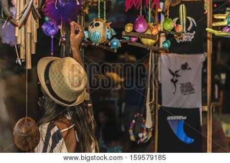 Urban scene of young adult black woman watching souvenirs at street store in Pipa Brazil