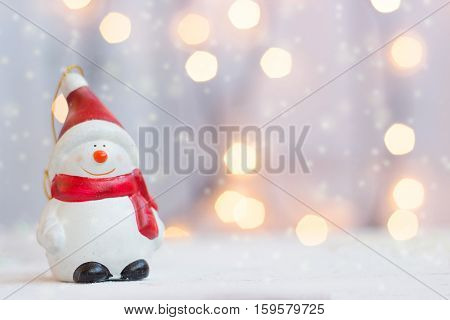 Christmas and new year background - snowman figurine against christmas lights, with copy space