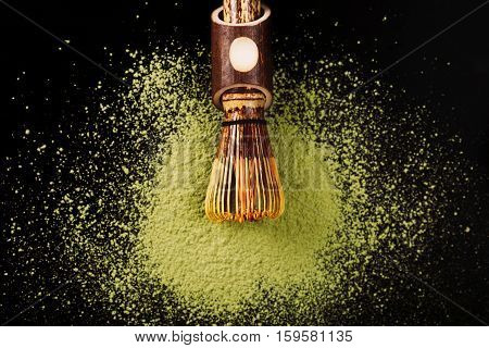 Chasen, special bamboo matcha tea whisk lying on powdered matcha on black surface.