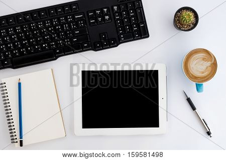 Modern White office desk table with blank screen tablet leather notebook pencil keyboard and cup of coffee. Top view with copy space.Office supplies and gadgets on worktable.Working desk table concept.