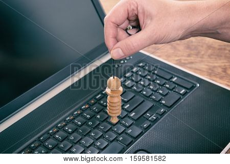 Hand with pendulum dowsing over laptop pc to check its quality, dangerous influence or radiation