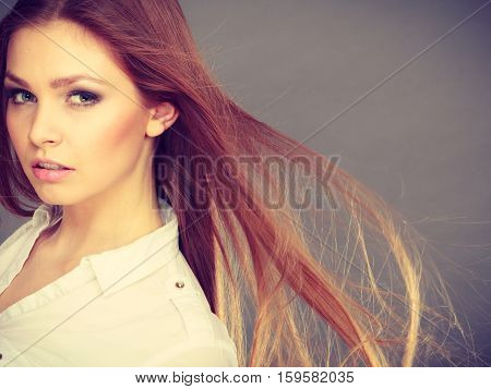 Haircare beauty hairstyling concept. Portrait of young attractive brunette woman wearing white shirt having windblown beautiful long brown hair.