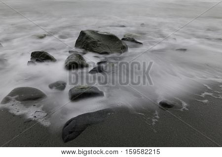 Water flowing around rocks on an ocean beach with sand Victoria British Columbia Canada