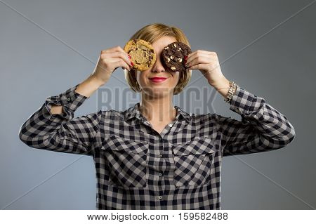 young blond cute and friendly caucasian woman in casual clothes holding big delicious two chocolate cookie looking with temptation as thinking if ignoring diet and eating sweet junk food isolated