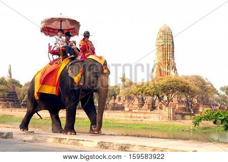 AYUTTHAYA ,THAILAND-APRIL 14,2016 :Unidentified Tourists riding on elephants along the way at Wat Phra Ram temple on Ayutthaya Historical Park , Ayutthaya old capital city in Middle of Thailand.