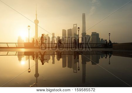 People running in morning at Huangpu River riverside with Shanghai downtown in background in Shanghai China.