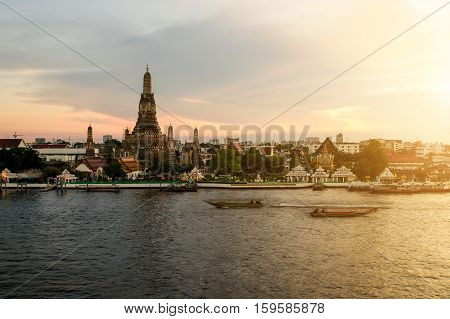 Wat Arun during sunset woth longtail boat in Chao Phraya river at Bangkok city Thailand