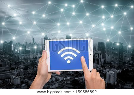 Hand holding tablet with wifi icon on city and network connection concept. Bangkok smart city and wireless communication network abstract image visual internet of things.
