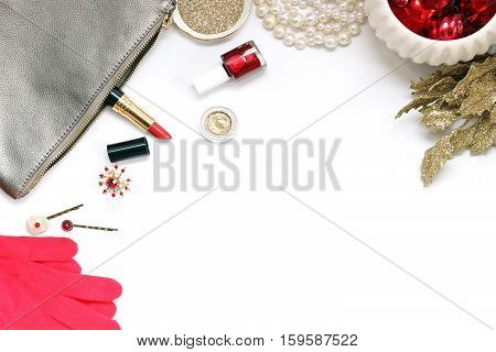 Over head flat lay view of a luxury vanity desk top. Silver, gold and red metallic. Cosmetics, jewelry, glitter, ornaments, mittens and glittered leaves. Open space for text.