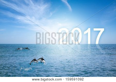 Happy school of bottlenose dolphins jumping over sea waves with happy new year background. The Number 2017 standing on Horizon with clear blue sky and surface of sea. Happy New Year conceptual image with copy space.