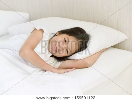 Portrait of happy young Asian girl lying on the bed after waking up and smiling under white blanket in the morning after good night sleep. Cheerful kid or preteen model with relaxing in the morning.