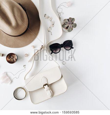 Flat lay trendy creative feminine accessories arrangement. Purse hat sunglasses female accessories. Top view